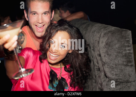 Portrait of enthusiastic couple drinking cocktail in nightclub - Stock Photo