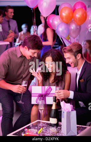 Smiling friends drinking champagne and celebrating birthday in nightclub - Stock Photo