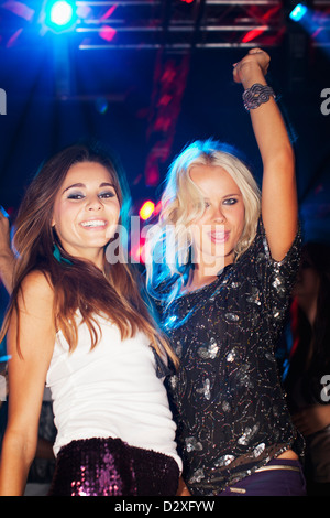 Portrait of smiling women dancing in nightclub - Stock Photo