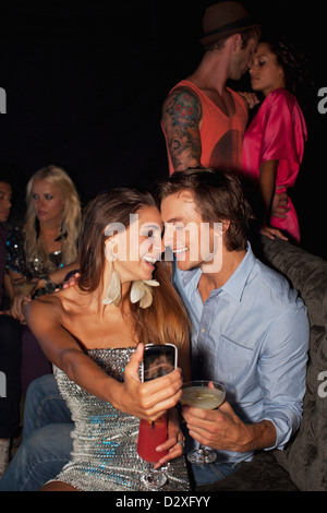 Smiling couple drinking cocktails and taking self-portrait with camera phone in nightclub - Stock Photo