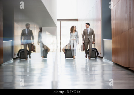 Businessman and businesswoman pulling suitcases through corridor - Stock Photo