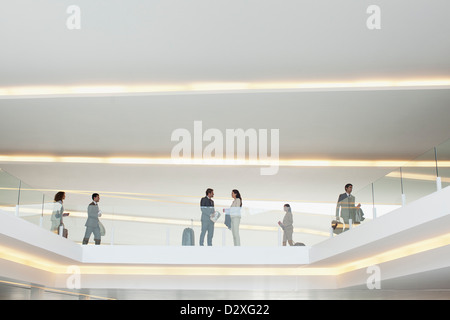 Business people on elevated walkway in airport - Stock Photo