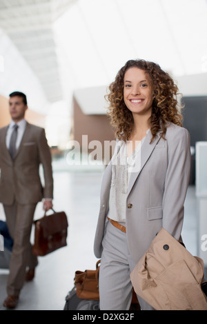 Portrait of smiling businesswoman with suitcase at airport - Stock Photo