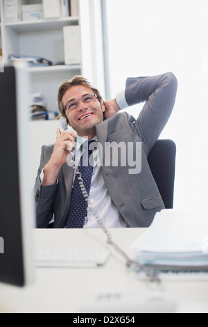 Smiling businessman talking on telephone at desk in office - Stock Photo