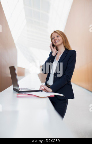 Smiling businesswoman talking on cell phone and using laptop in office - Stock Photo
