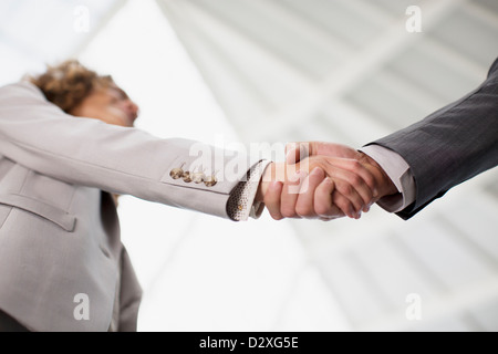 Close up of businessman and businesswoman shaking hands - Stock Photo