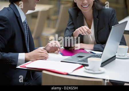 Smiling businessman and businesswoman using laptop in cafe - Stock Photo
