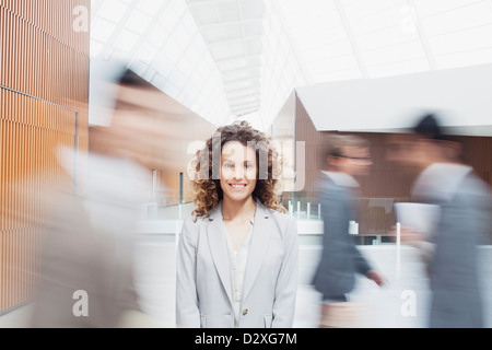 Portrait of smiling woman with co-workers rushing by in lobby - Stock Photo