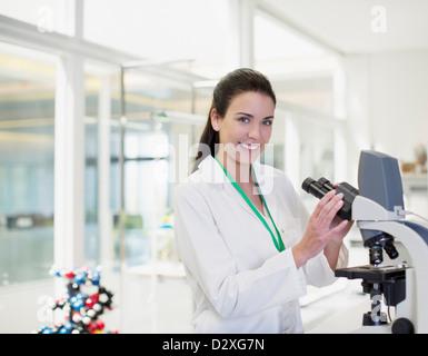 Portrait of confident scientist using microscope in laboratory - Stock Photo