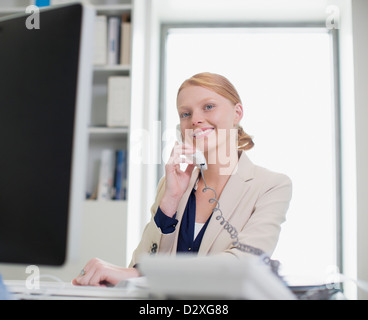 Portrait of confident businesswoman using computer and talking on telephone - Stock Photo