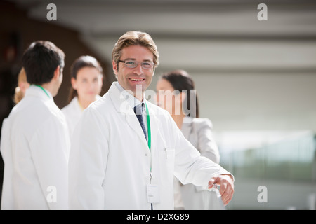 Portrait of smiling scientist with co-workers in background - Stock Photo