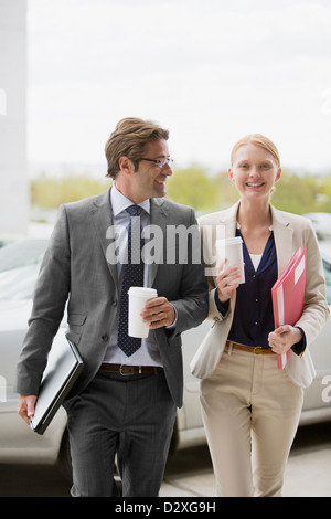 Smiling businessman and businesswoman walking with coffee cups - Stock Photo