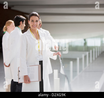 Portrait of smiling doctor with clipboard - Stock Photo