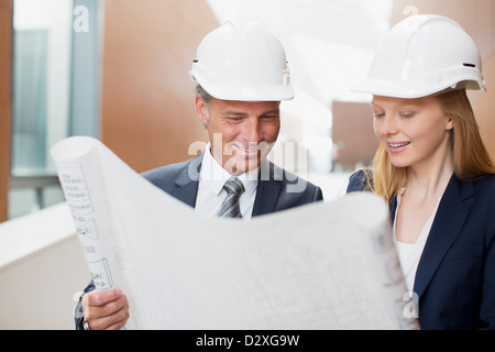 Architects wearing hard-hats and reviewing blueprints - Stock Photo