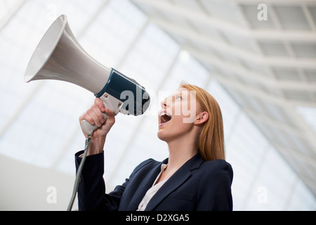 Businesswoman shouting into bullhorn - Stock Photo