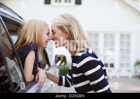 Mother and daughter touching noses in car - Stock Photo