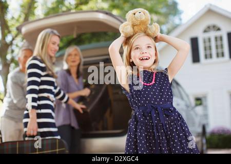 Girl carrying teddy bear on her head - Stock Photo