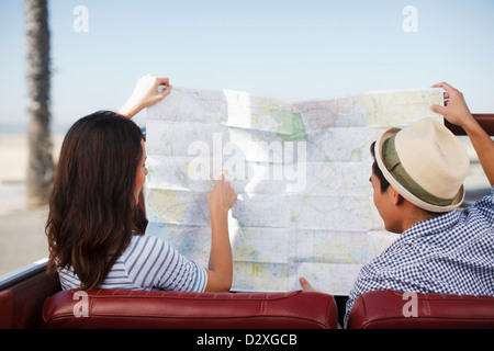 Couple reading road map in convertible - Stock Photo