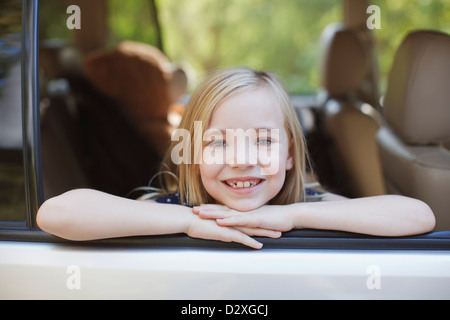 Smiling girl leaning out car window - Stock Photo