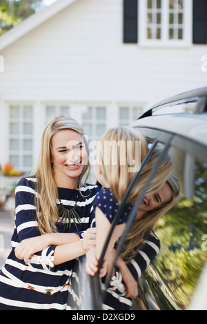 Mother talking to daughter in car window - Stock Photo