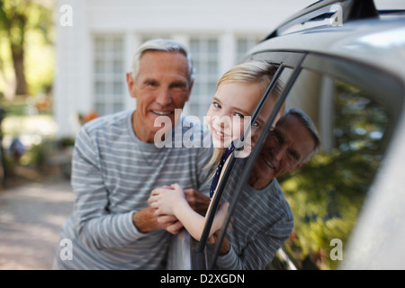 Older man talking to granddaughter in car window - Stock Photo