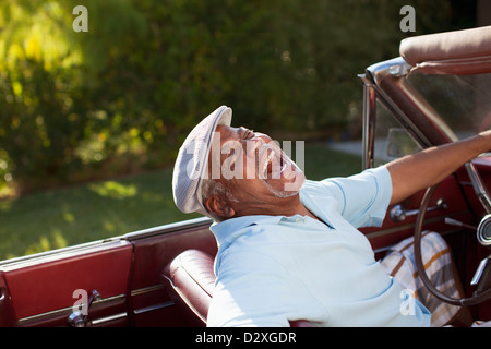 Laughing older man driving convertible - Stock Photo