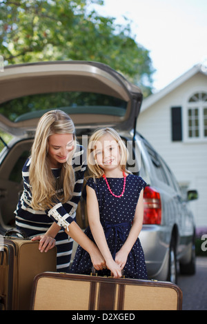 Mother and daughter carrying luggage to car - Stock Photo