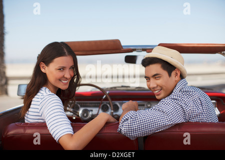 Smiling couple sitting in convertible - Stock Photo