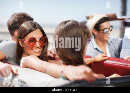Friends driving in convertible - Stock Photo