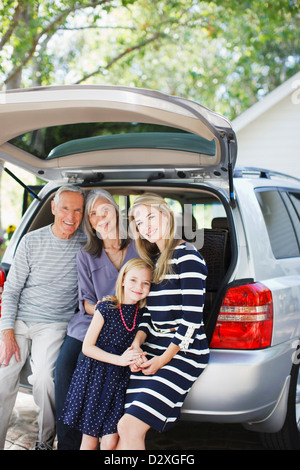 Family sitting in trunk of car - Stock Photo