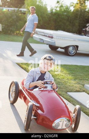 Smiling boy playing in go cart - Stock Photo
