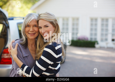 Mother and daughter hugging outdoors - Stock Photo
