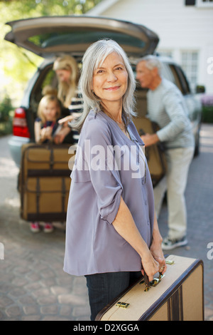 Woman carrying suitcase to trunk - Stock Photo