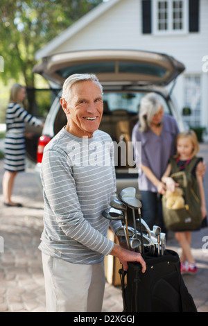 Older man carrying golf clubs in bag - Stock Photo