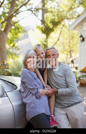 Older couple and granddaughter leaning on car - Stock Photo
