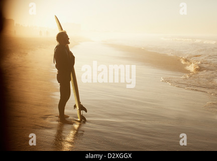 Surfer standing with board on beach - Stock Photo