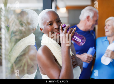 Older woman drinking water after workout - Stock Photo