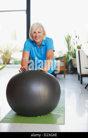 Older woman using exercise ball in home - Stock Photo