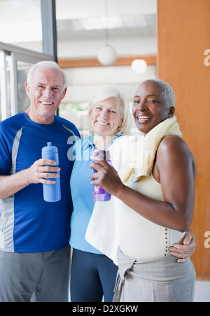 Older people drinking water after workout - Stock Photo