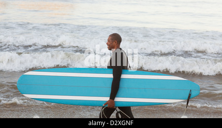 Older surfer carrying board on beach - Stock Photo