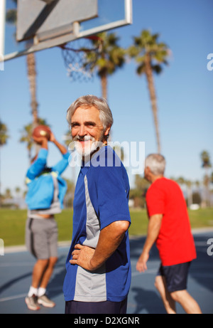 Older man playing basketball on court - Stock Photo