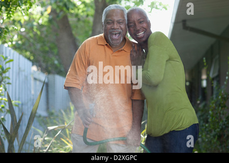 Older couple watering plants in backyard - Stock Photo
