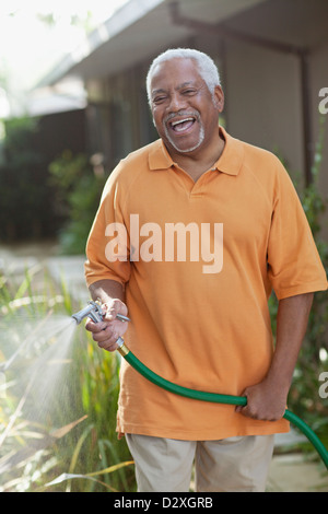 Older men watering plants in backyard - Stock Photo