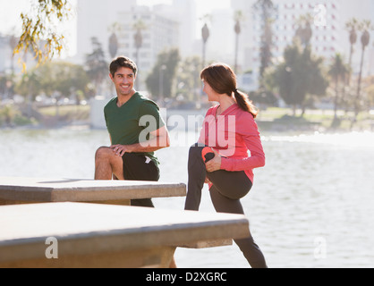Couple stretching together in park - Stock Photo