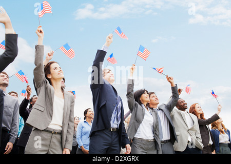 Smiling business people in crowd waving American flags - Stock Photo