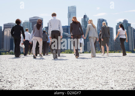 Business people walking toward city - Stock Photo