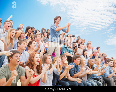 Man standing and clapping among cheering crowd - Stock Photo