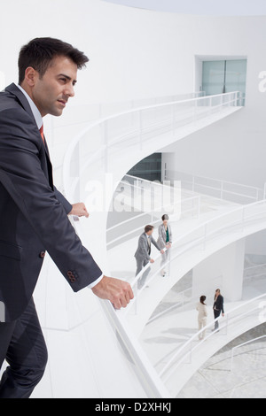 Pensive businessman leaning on railing of elevated walkway - Stock Photo