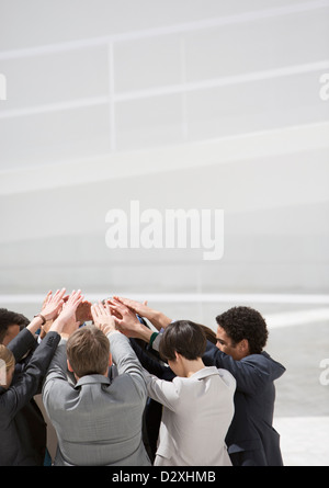 Business people with arms raised in huddle - Stock Photo