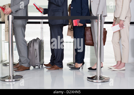 Business people standing in queue at airport - Stock Photo